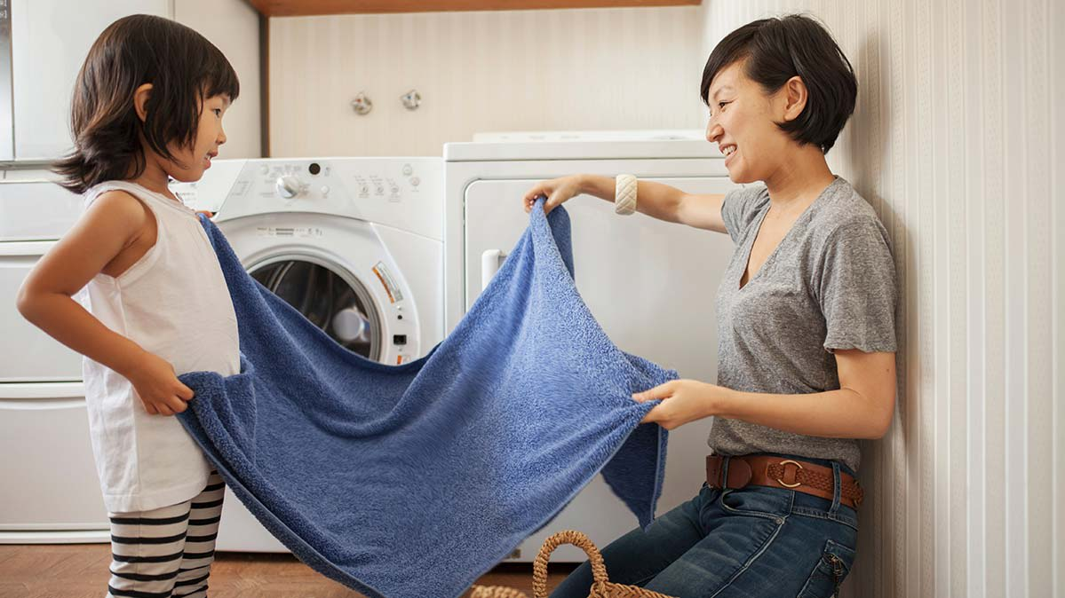 A mother and her daughter are folding clothes in front of a washer and dryer.