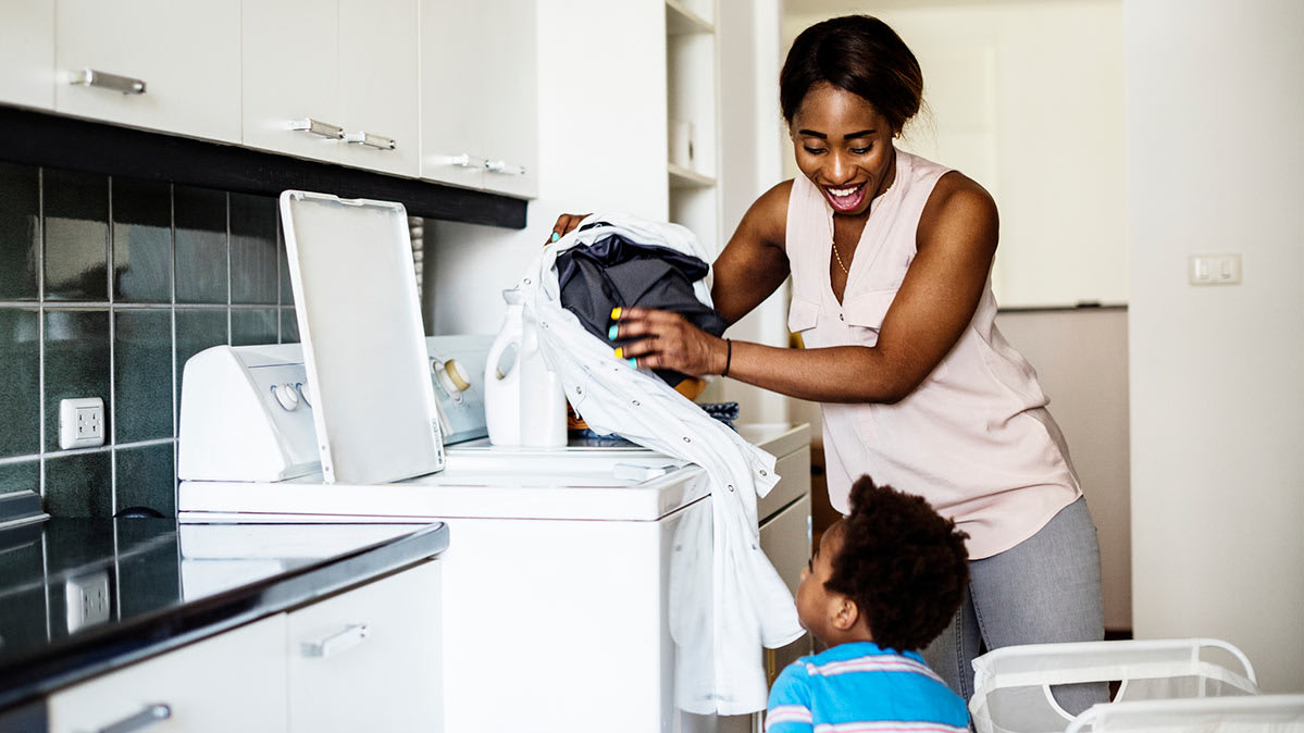 A woman is putting laundry into a top-load washing machine while a child looks on.