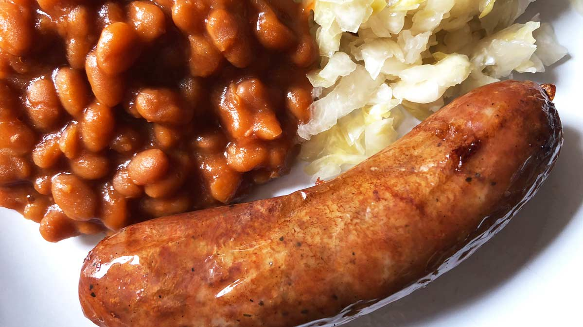 A plate of bratwurst, slaw, and baked beans.