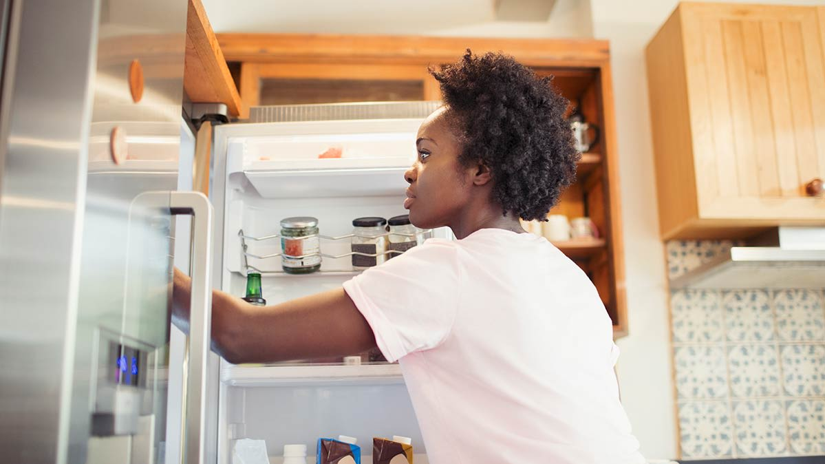 A woman taking something out of a refrigerator in her kitchen