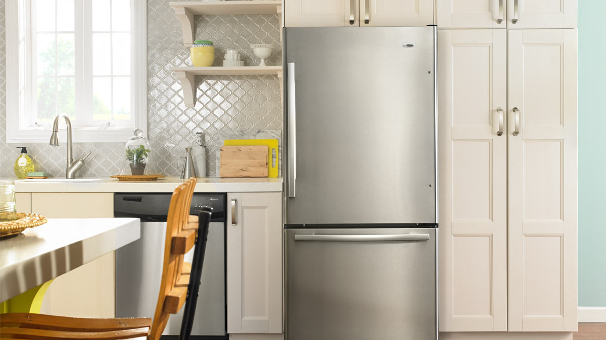 A kitchen with a bottom-freezer refrigerator