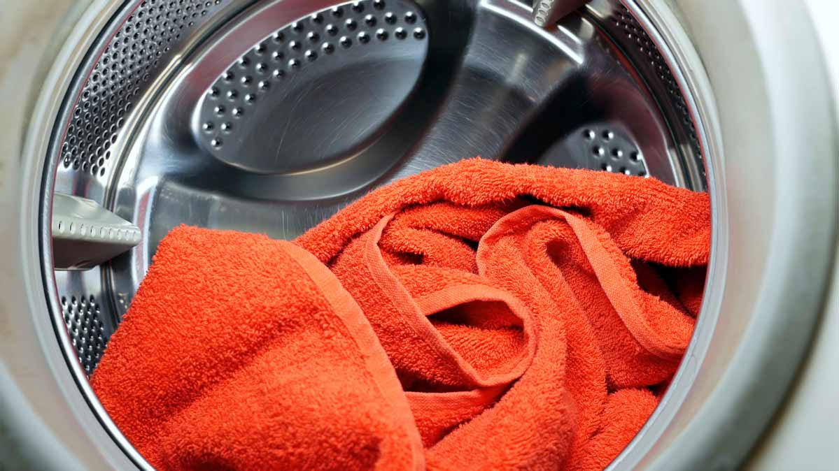 An orange towel in a front-loading washing machine