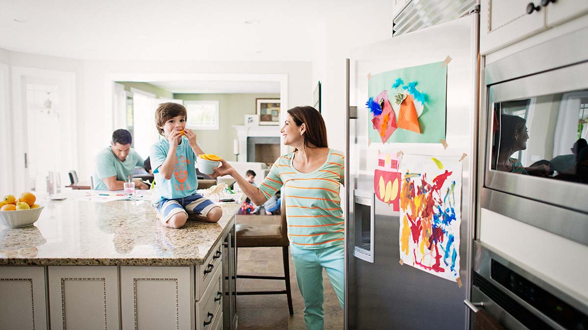 Image of family in their kitchen fitted with a large refrigerator