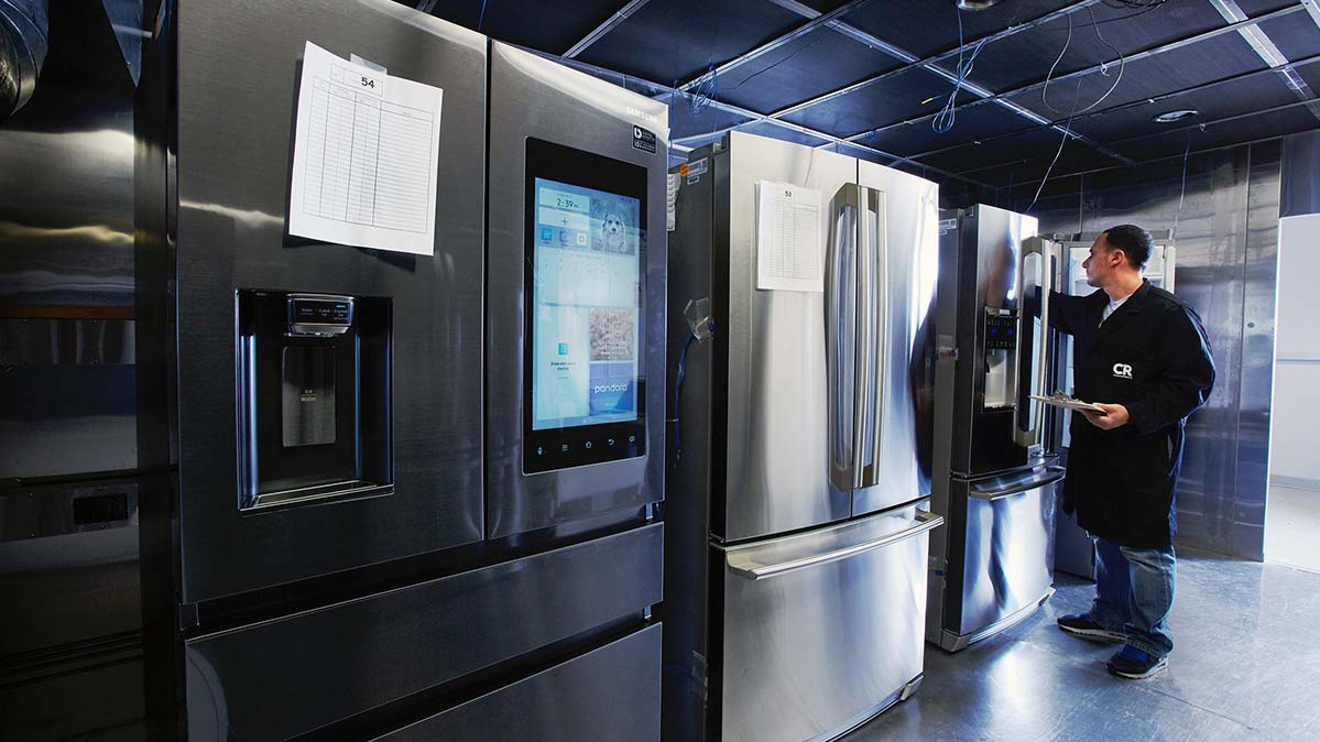 A row of refrigerators in CR's refrigerator test lab, with a test engineer evaluating the interior of one model.