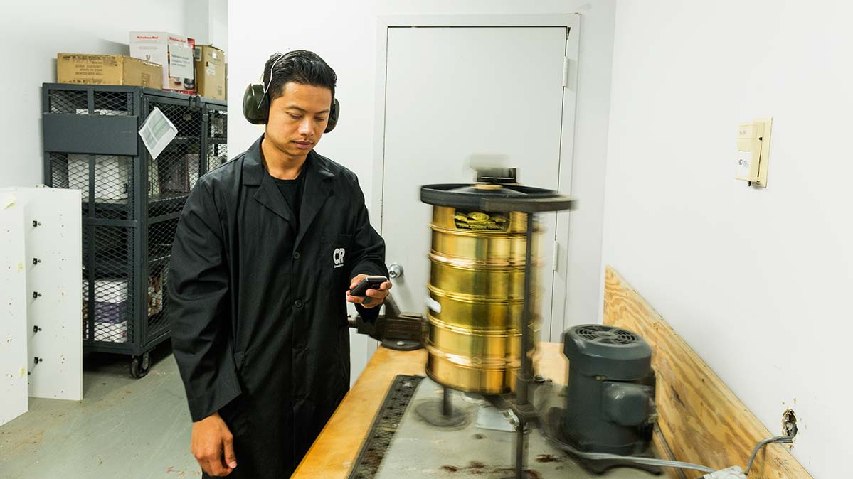 A CR test technician uses a shaker to disperse coffee grounds through a set of sieves.