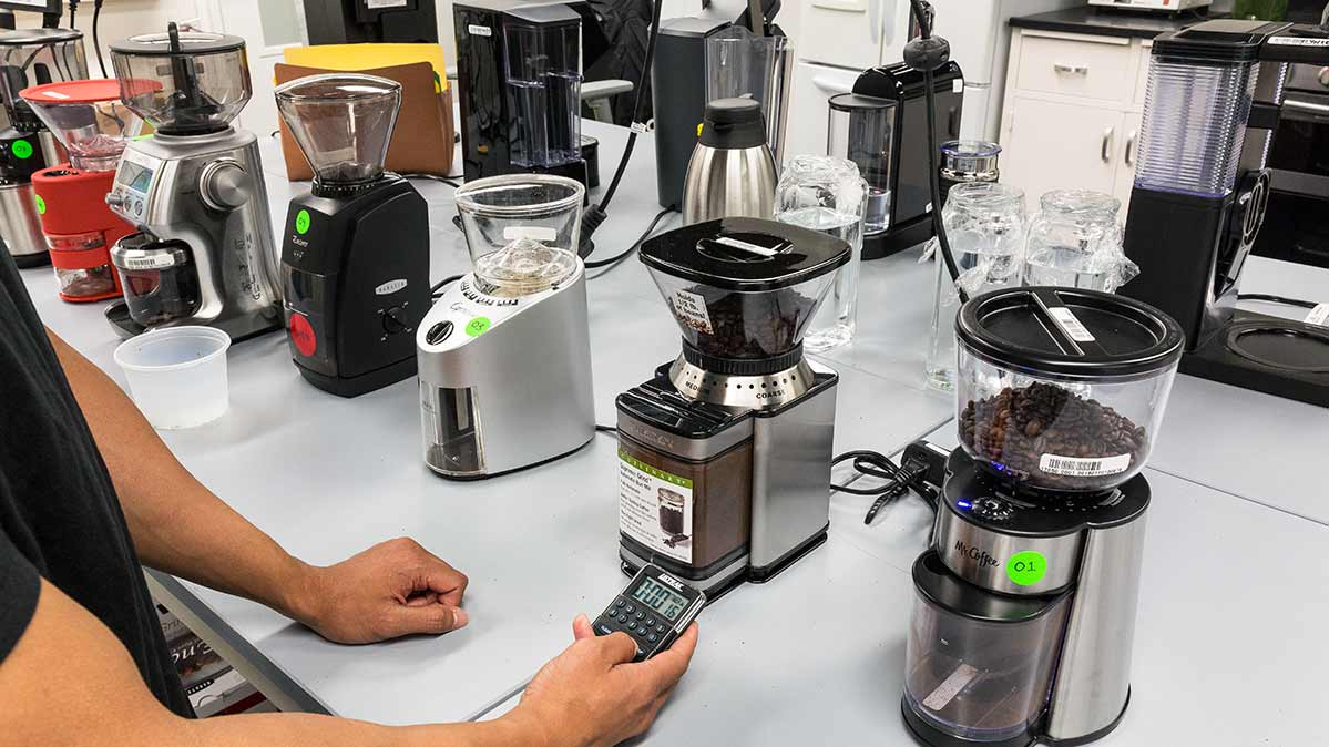 A CR test technician times some of the best coffee grinders from our tests.