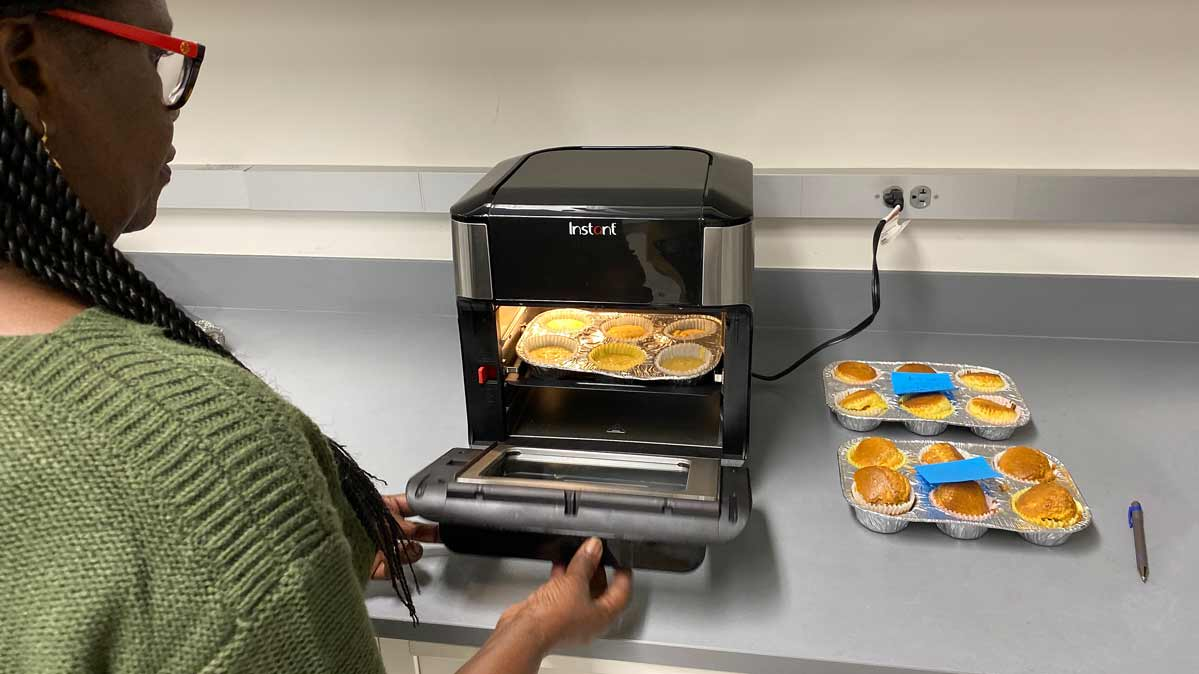 Tester Ami Ndiaye puts corn muffins in the Instant Vortex Plus as part of CR's baking tests. She uses a colorimeter to measure the muffins' color evenness.