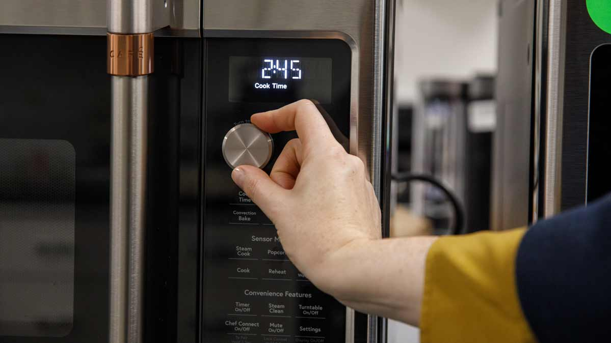 A Consumer Reports technician testing a microwave oven in CR's lab