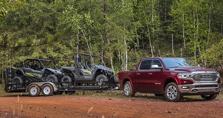2020 Ram 1500 towing a trailer with side-by-sides