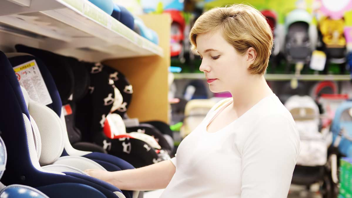 A woman examining a car seat to see if the car seat meets U.S. standards.