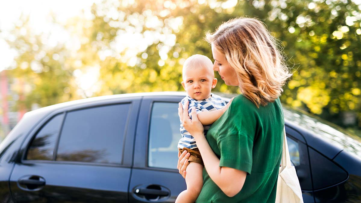 A woman holding an infant while standing next to a car