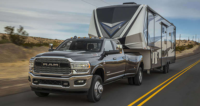 A Ram 3500 pickup truck pulling a fifth-wheel trailer.