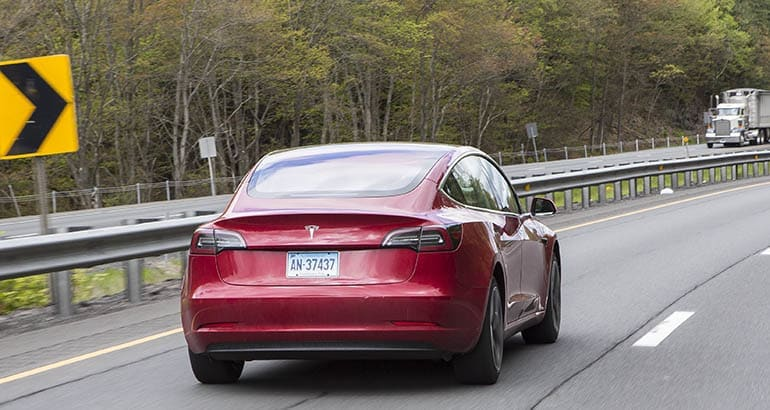 Tesla Model 3 on highway, from rear