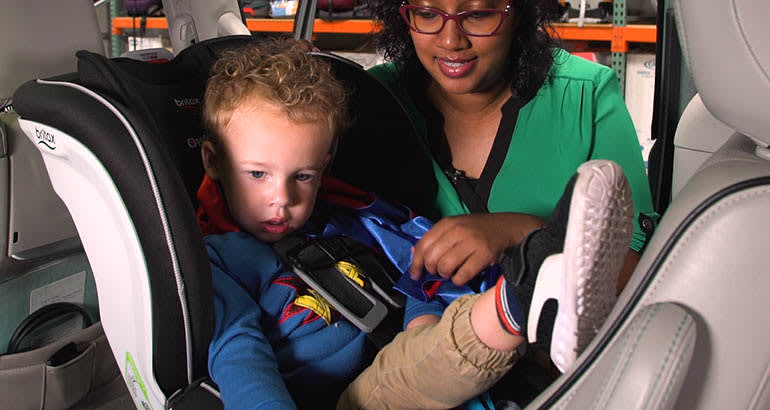 Child being buckled into a car seat
