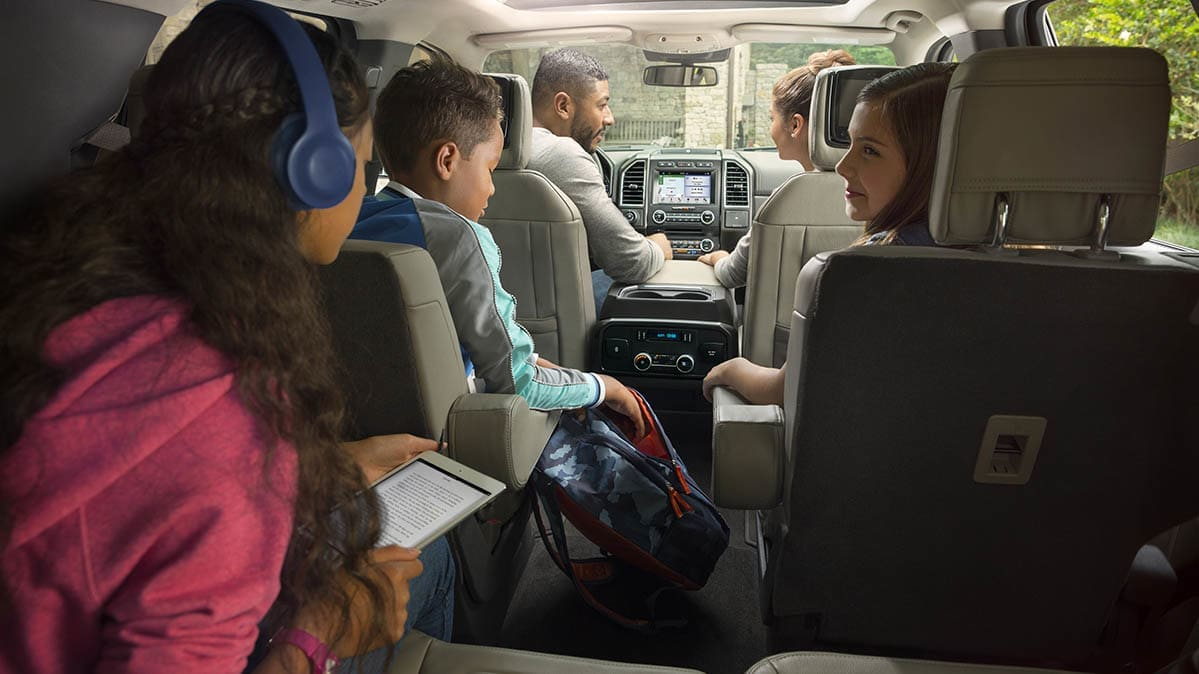 A family sitting inside a 3-row SUV