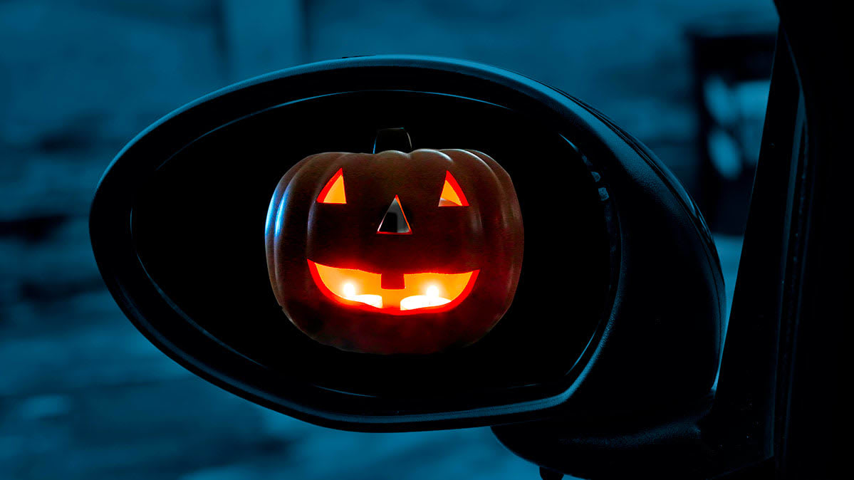 A jack-o'-lantern in the sideview mirror of a car.