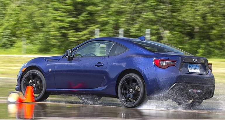 Consumer Reports tire testing, showing a Toyota 86 from the rear on wet pavement