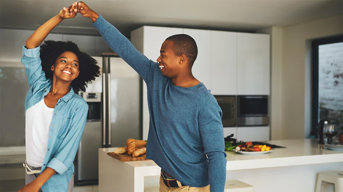 A couple dancing in a kitchen.