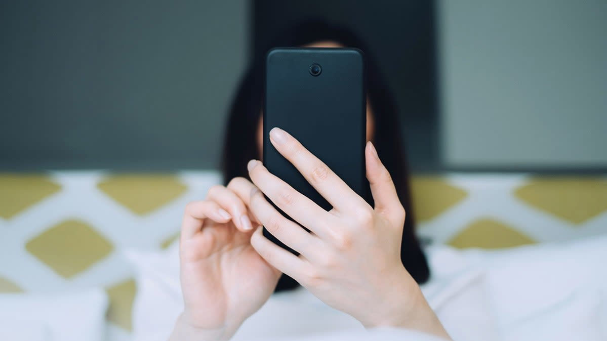 A person holding a smartphone in here hand in front of her face