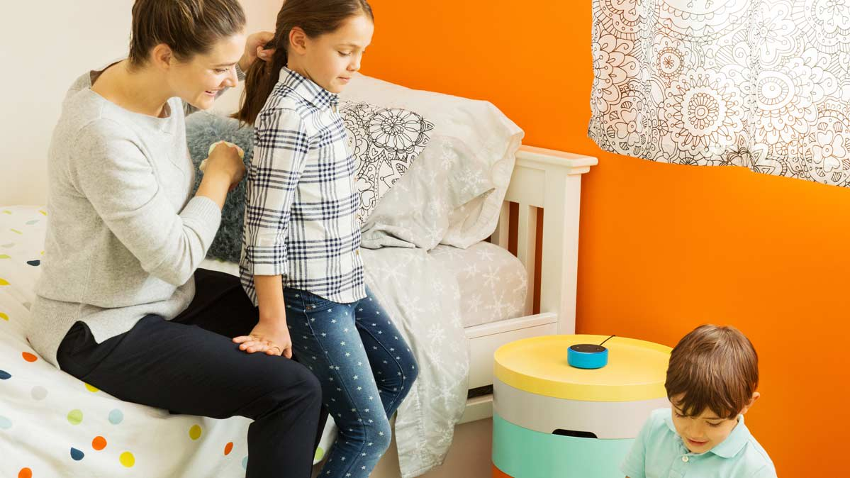 Amazon Echo Dot Kids Edition speaker in a family setting with a parent and children