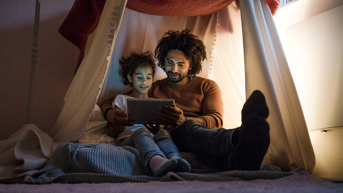 A father and daughter in a tent looking at a tablet.