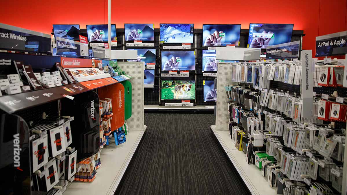 Long aisle view of tech accessories and wall of flat-screen TVs at Target