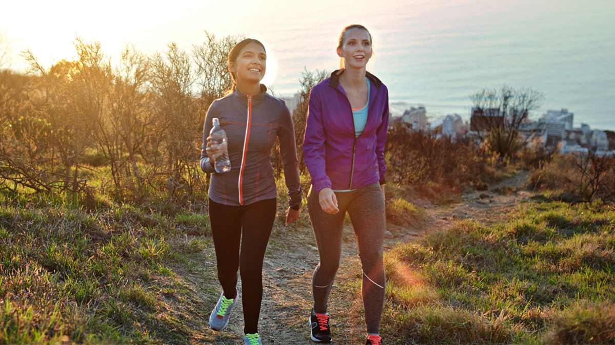 Two women walk along a sunny trail outdoors in workout clothing.