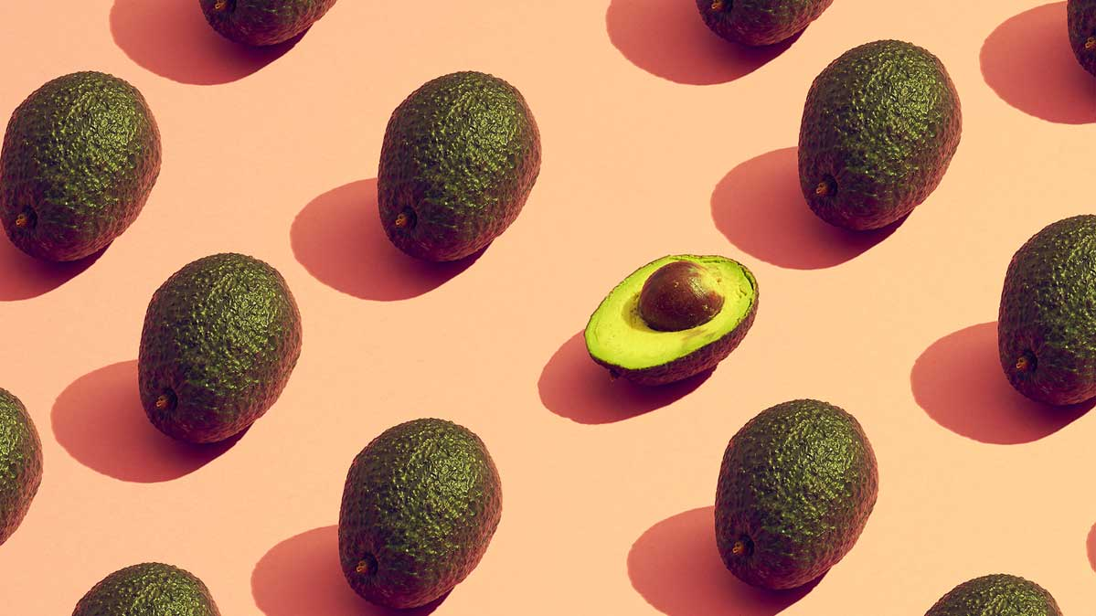 An image of several avocados spaced evenly on a surface. One is only half of an avocado.