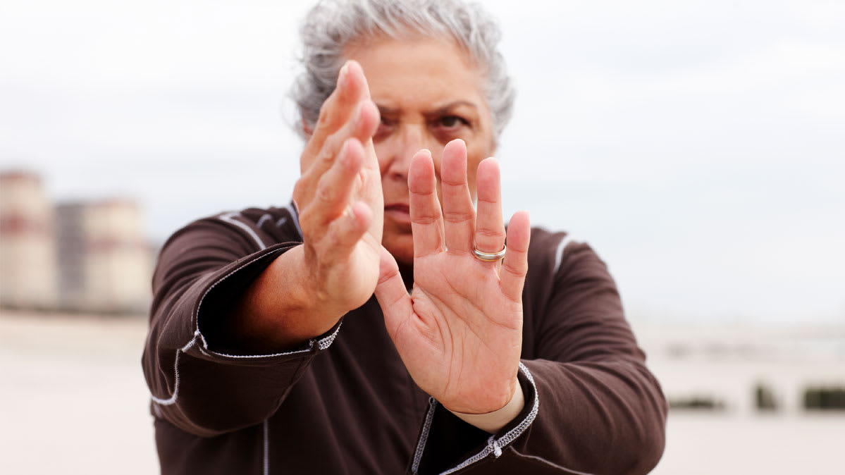 An older woman practicing tai chi.