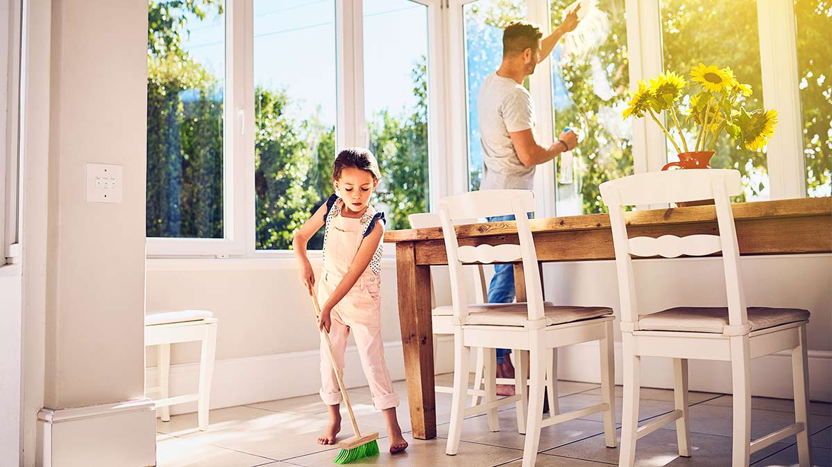 Photo of parent and child cleaning a home