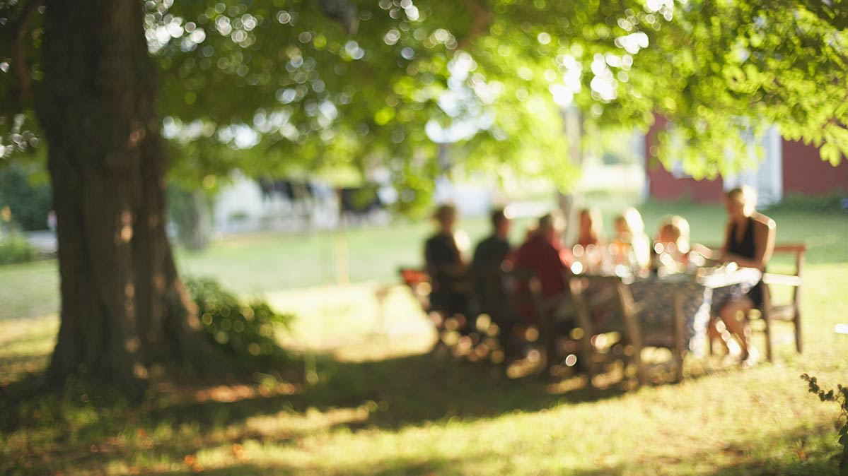 A blurry image of a group eating outdoors.