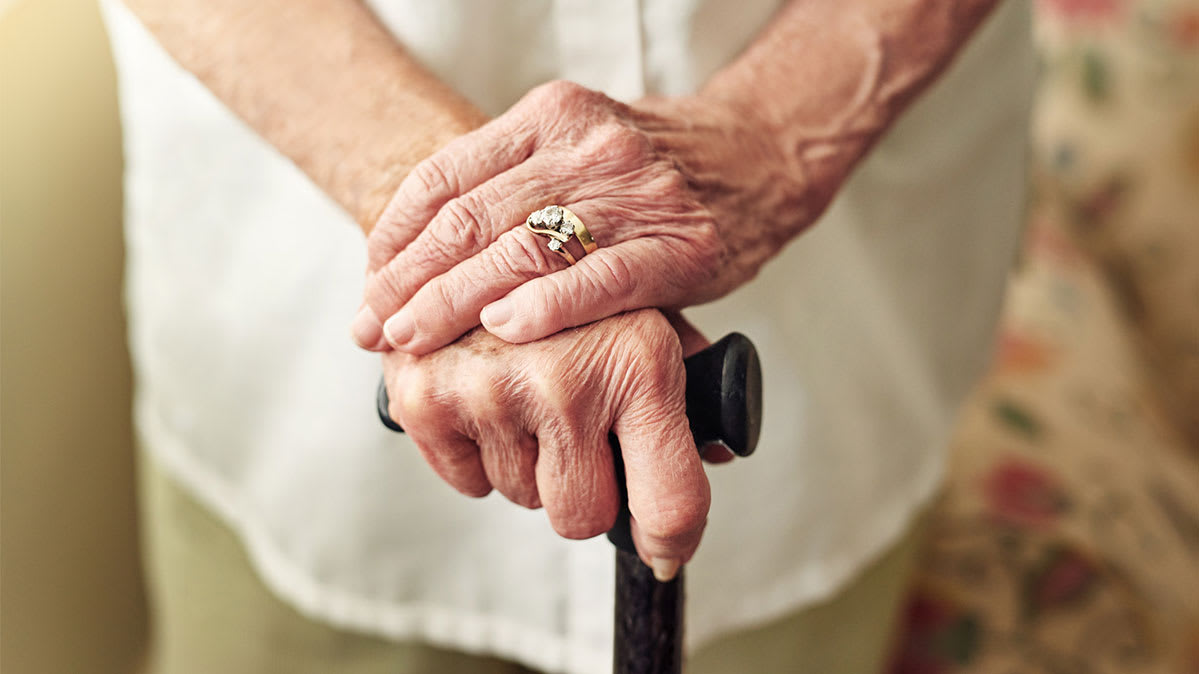 The hands of an elderly person holding the top of a cane