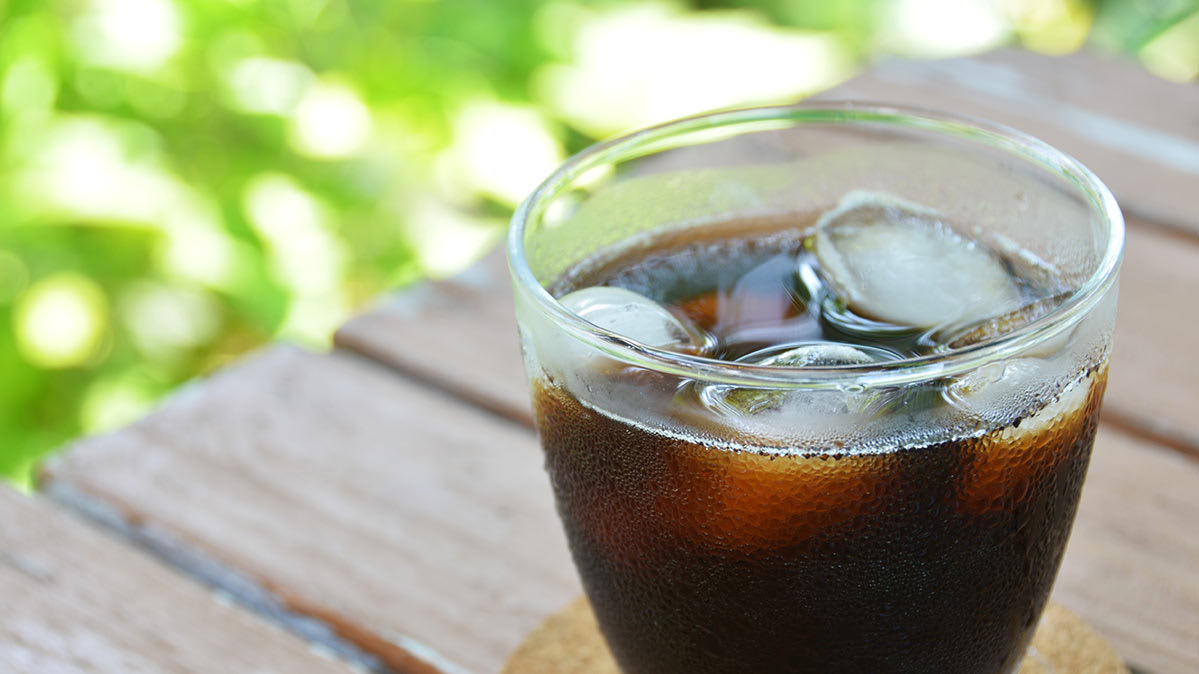 A glass of cold-brew coffee with ice cubes on an outdoor table