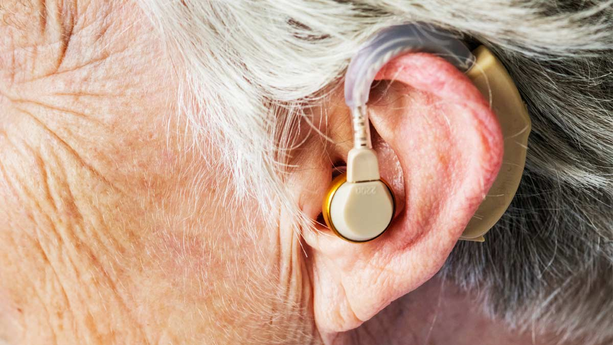 A close-up photograph of a hearing aid in a person's ear.