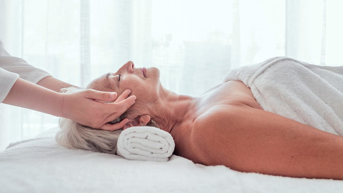 A woman in a towel lies face up on a massage table