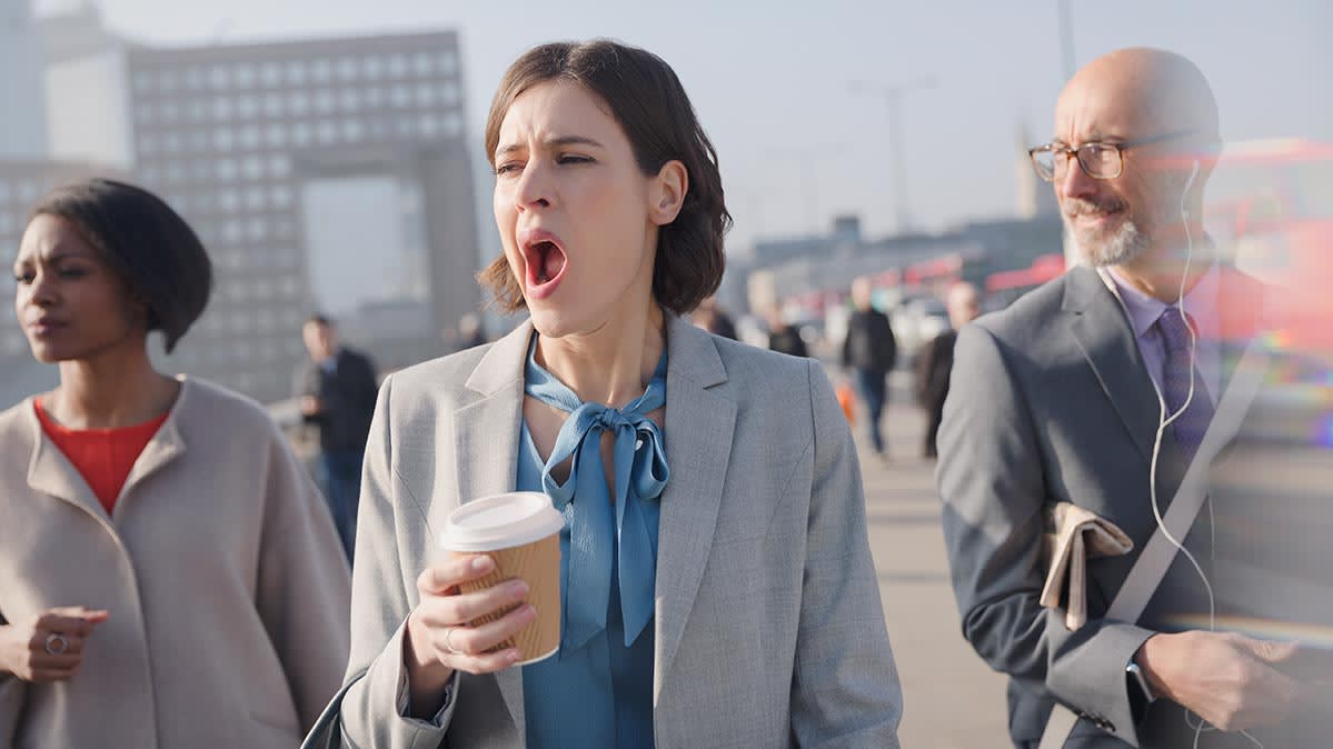 A woman yawning while holding a cup of coffee