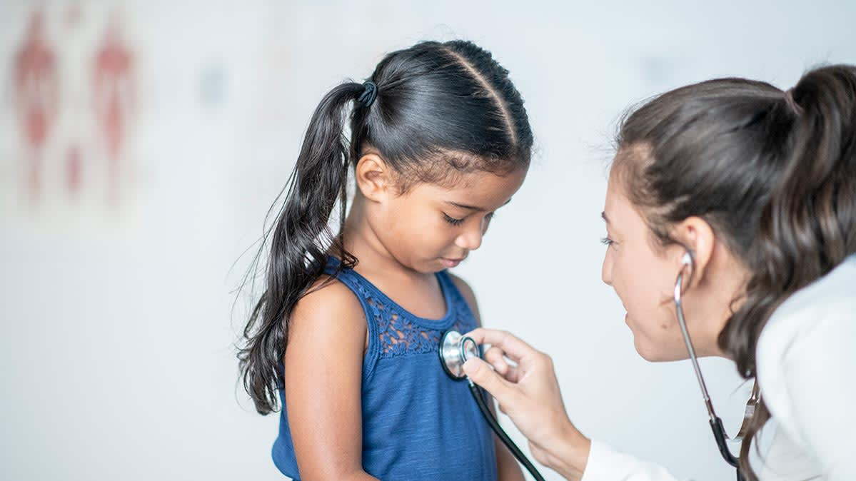 A school nurse listens to a student's chest with a stethoscope.