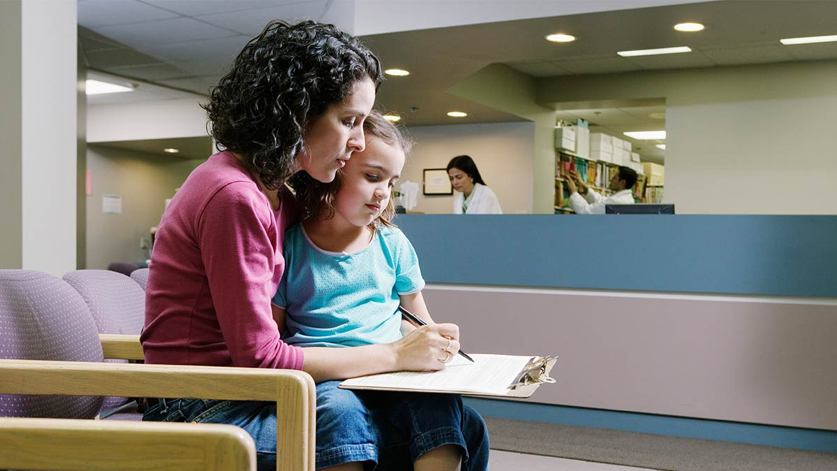 Adult woman with dark hair and little girl sitting on her lap as she fills out medical forms.