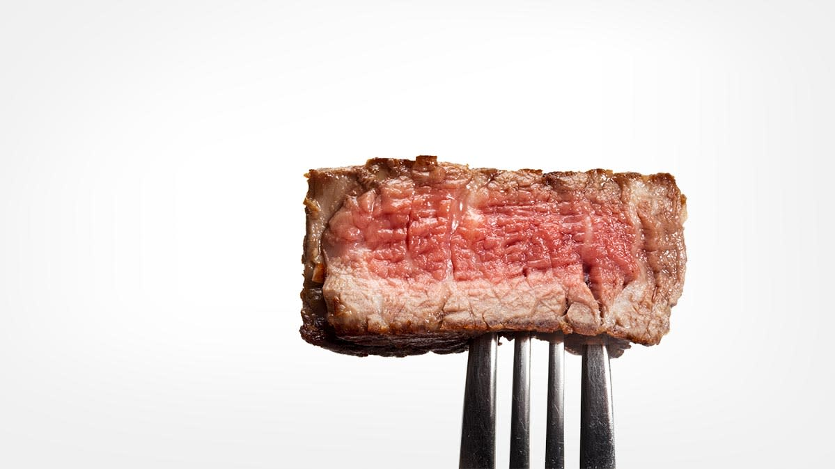 A piece of red meat on the tip of a fork