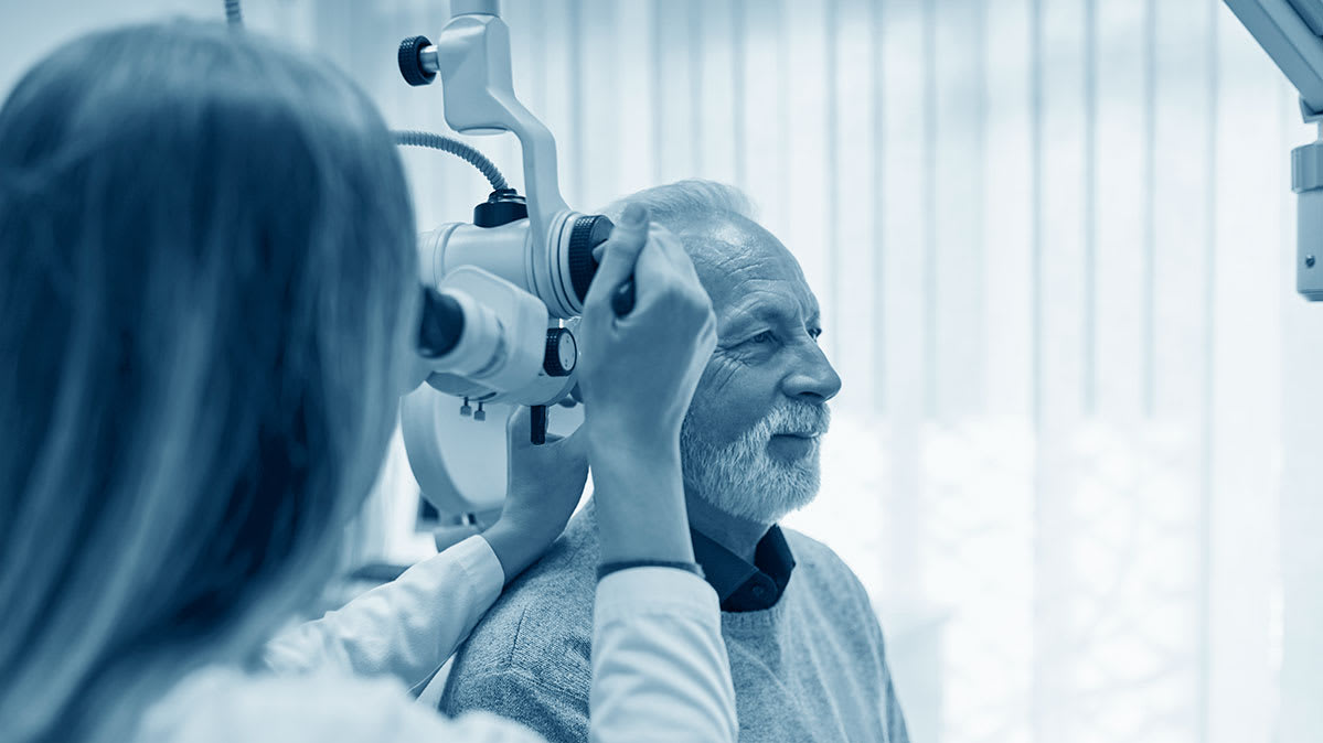An older man receives an ear exam.