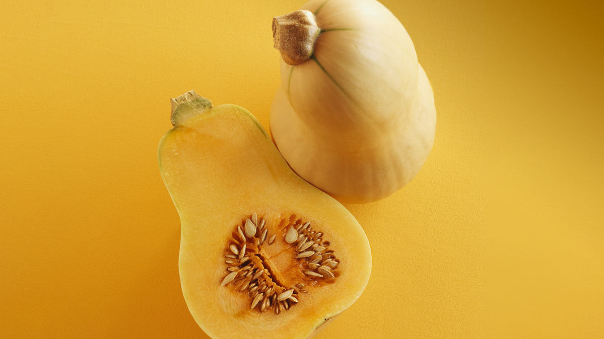 A butternut squash sliced in half on a golden background.