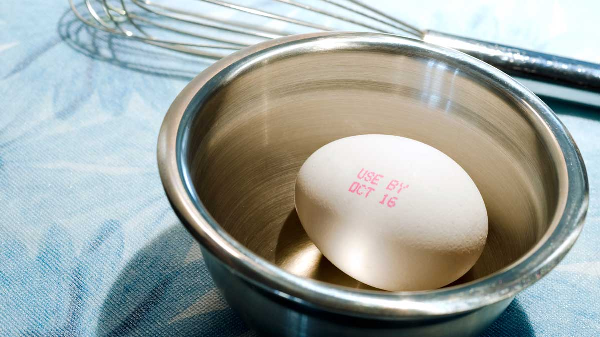 Egg with an expiration date on it in a mixing bowl.