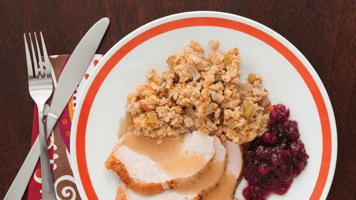 Plate of turkey with gravy, stuffing, and cranberry.