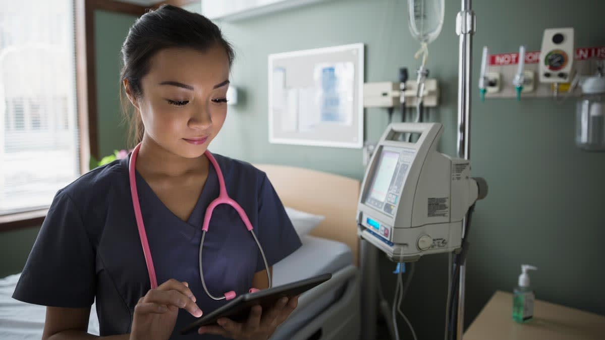 A hospital professional in navy scrubs looks at a tablet