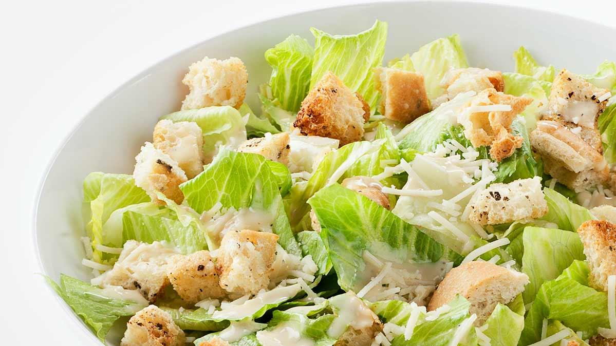 A photo of a Caesar salad with romaine lettuce