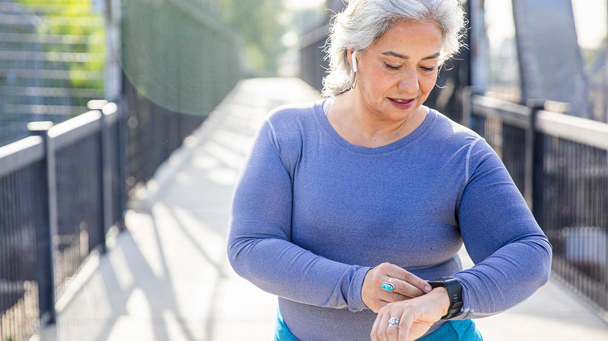 An older woman checks an activity tracker on her wrist during a workout.