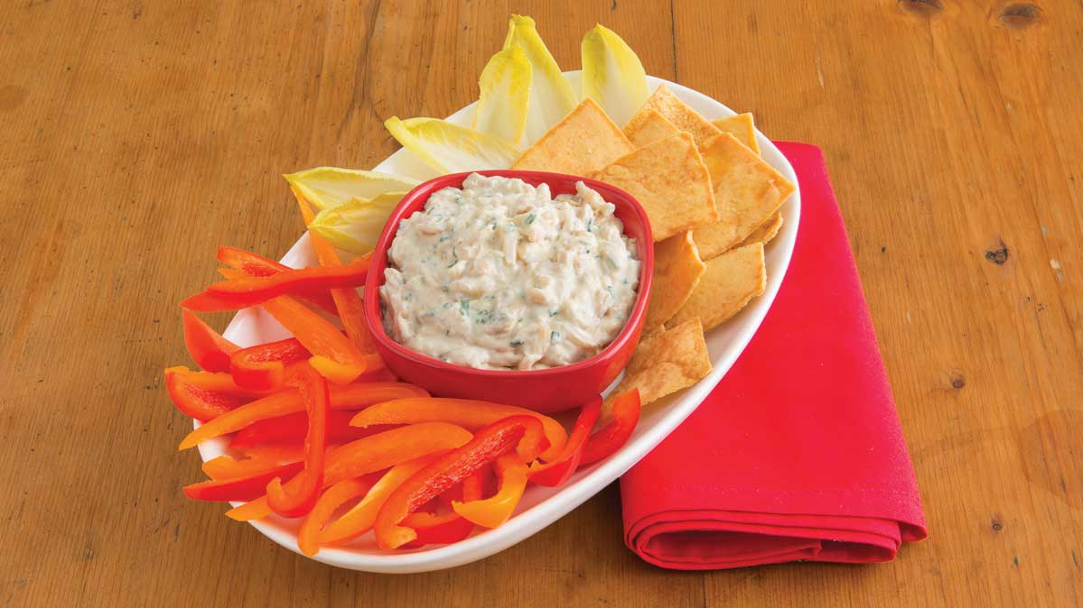 A platter of healthy dips, vegetables, and pita chips.