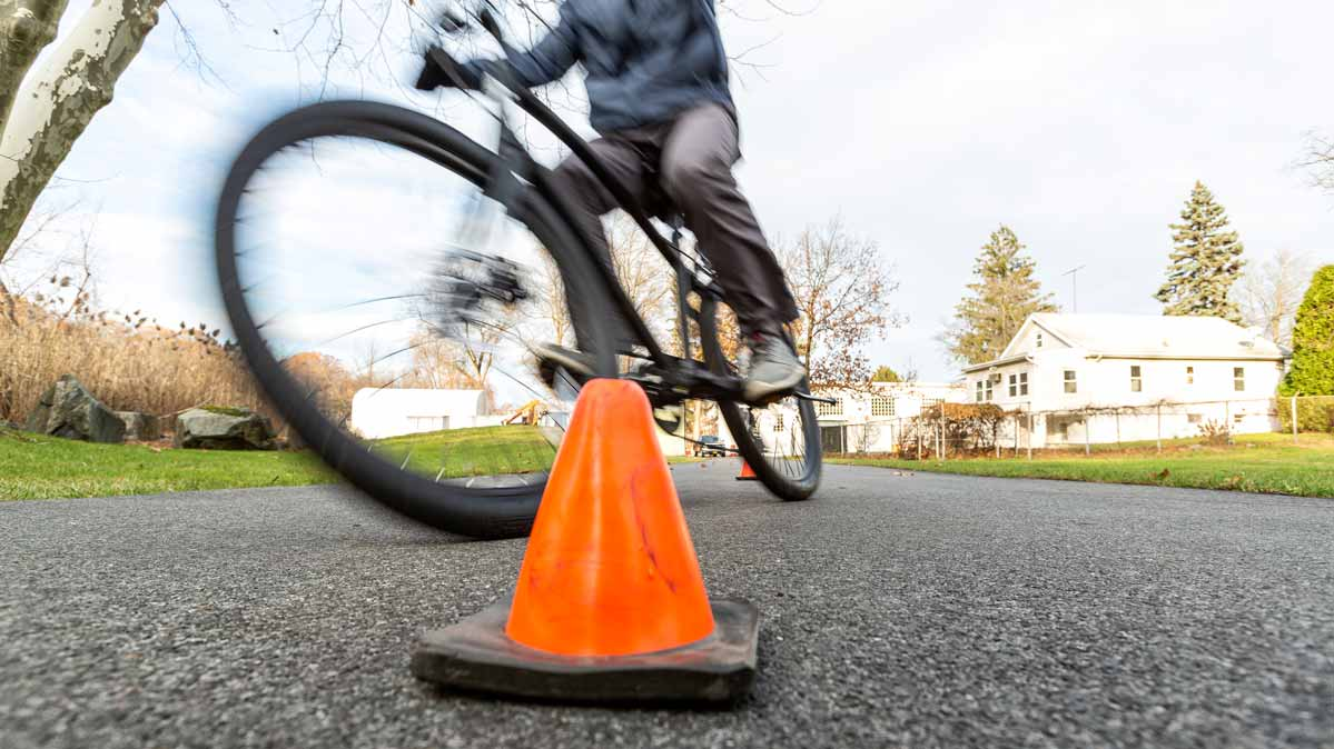 A person on an electric bike goes around an orange traffic cone.