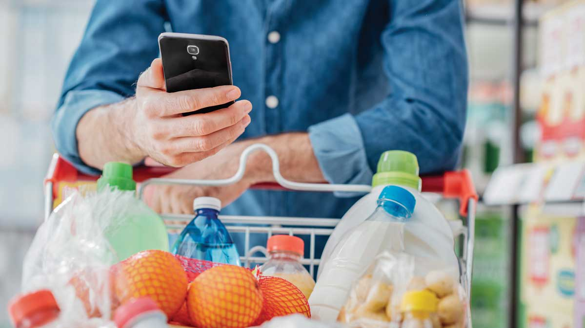 A person consulting a smartphone while grocery shopping.