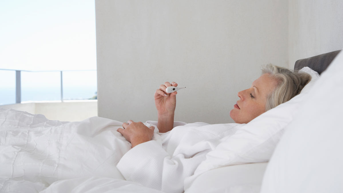 A woman in bed with flu complications looking at a thermometer.